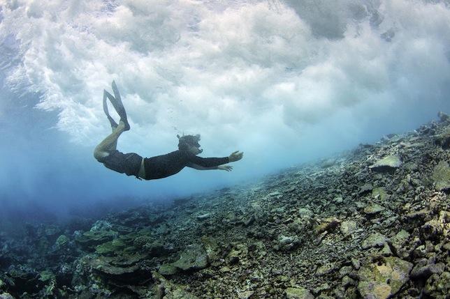 Дайвер проплывает над гребнем рифа, рассекающим волну у атолла Пальмира